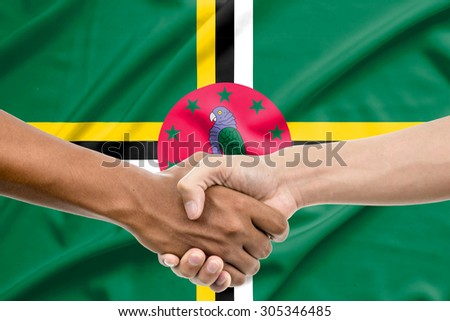 Handshake - Hand holding on Dominica flag background - stock photo