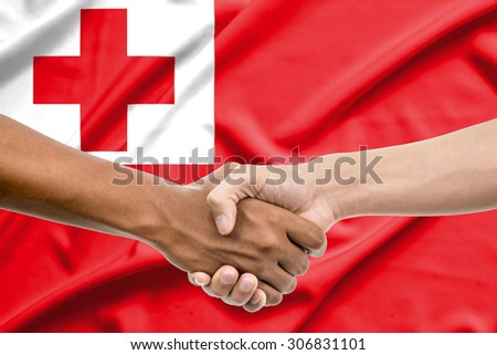 Handshake - Hand holding on tonga flag background - stock photo
