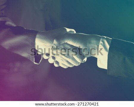 Handshake Handshaking dark and light, sepia tone - stock photo