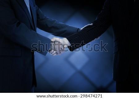 Handshake in agreement against dark grey room - stock photo