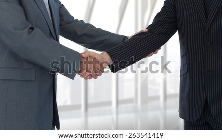 Handshake in agreement against room with large window looking on city - stock photo