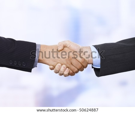 Handshake in closeup in business situation in office. - stock photo