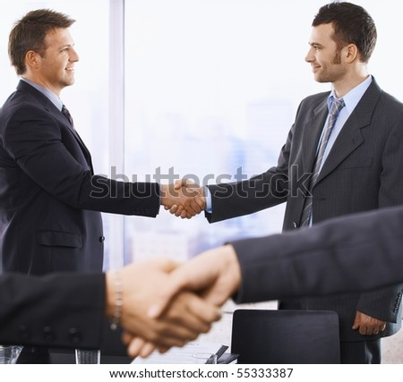 Handshake in closeup, smiling businessmen shaking hands in background of skyscraper office.? - stock photo