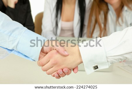 Handshake in front of business people.