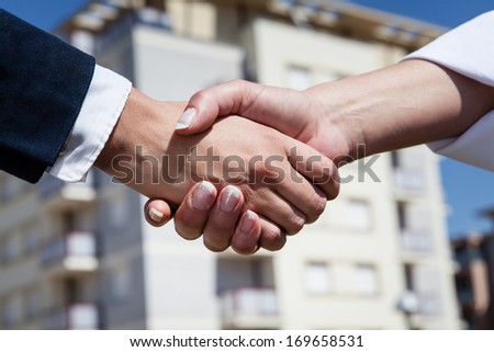 Handshake in the front of the new building - stock photo