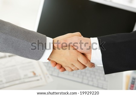 Handshake in the office over documents, computer in the background