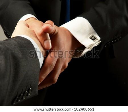 handshake isolated on black background - stock photo