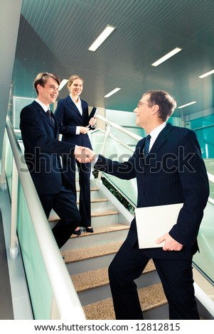 Handshake of business partners on the stairs of office building with smart woman standing behind - stock photo