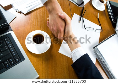 Handshake of business people over the workplace - stock photo