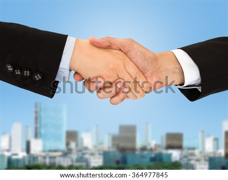 handshake of business people with a skyline city in background