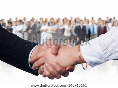 Handshake of business people with people at background