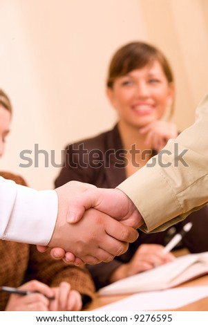 Handshake of business people with rest of team at unfocused background