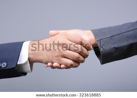 Handshake of businessman and businesswoman on light gray background - greeting, dealing, merger and acquisition concepts