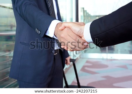 Handshake of businessmen at the airport - business travel concept - stock photo