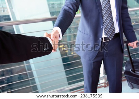 Handshake of businessmen at the airport - business trip concept - stock photo