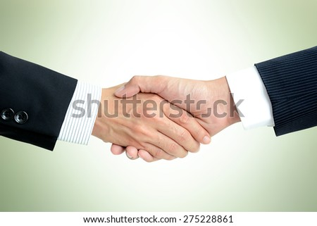 Handshake of businessmen in light green background - greeting , dealing, merger & acquisition concepts