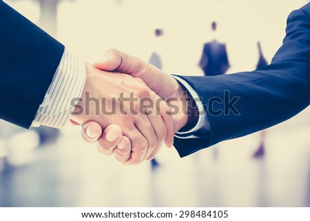 Handshake of businessmen on blur businesspeople background, vintage tone - greeting, dealing, merger and a acquisition concepts - stock photo