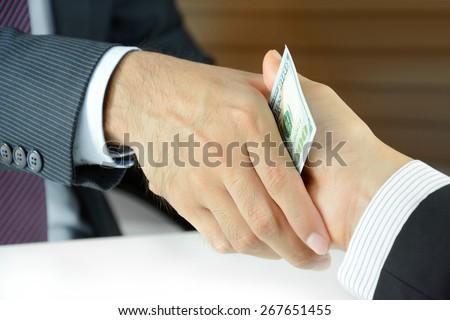 Handshake of businessmen with money - bribery concept - stock photo