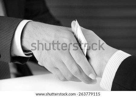 Handshake of businessmen with money, bribery concept - monochrome effect - stock photo
