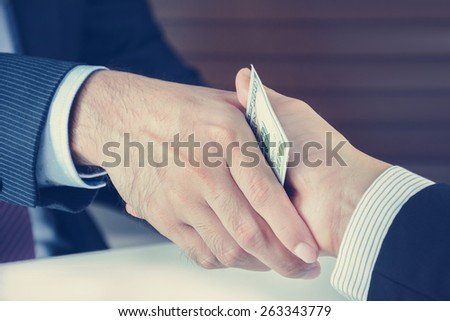 Handshake of businessmen with money, bribery concept - vintage tone - stock photo