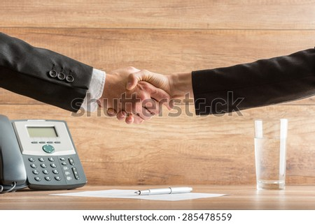 Handshake of two business partners after a successful meeting at the office, above a signed contract, placed on wooden desk, near the telephone. - stock photo