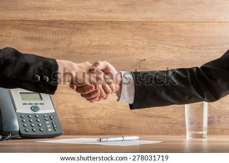 Handshake of two business partners after a successful negotiation at the office, above a written and signed agreement, placed on desk, near the telephone, with copy space on wooden wall. - stock photo