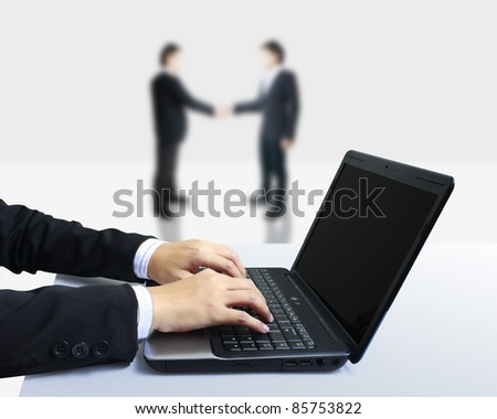 Handshake of two business with a laptop - stock photo