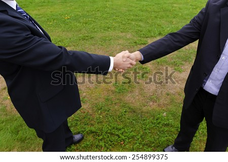 Handshake of two businessmen in suits - stock photo