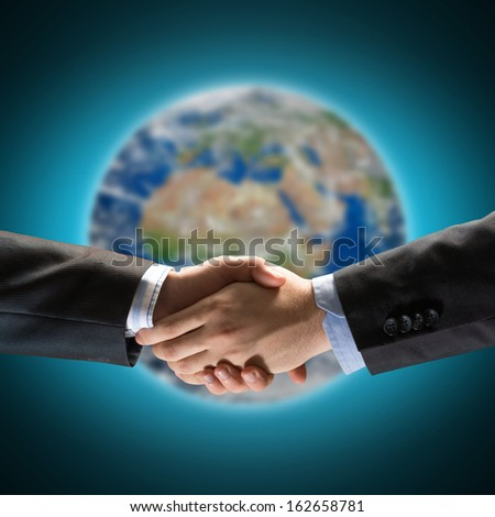handshake of two businessmen on the background of the planet earth. Elements of this image are furnished by NASA - stock photo