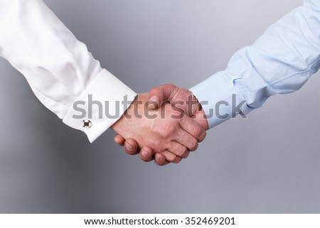 Handshake of two men in a white and blue shirt