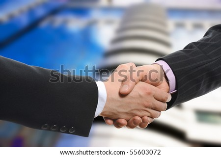 Handshake of two men in black suits on the background of the business building - stock photo
