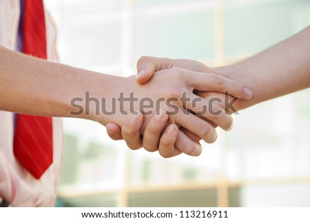 handshake of two persons near the building - stock photo