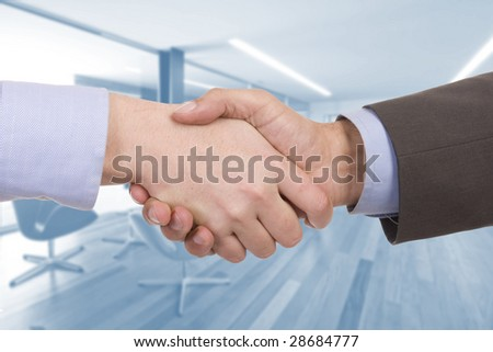 Handshake of two successful businesspeople (with office on background) - stock photo