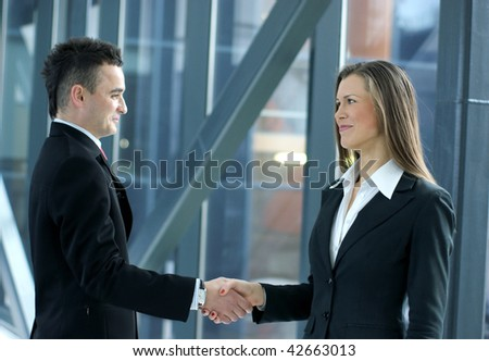Handshake of young business people over industrial background (Warning! No focus on man!) - stock photo