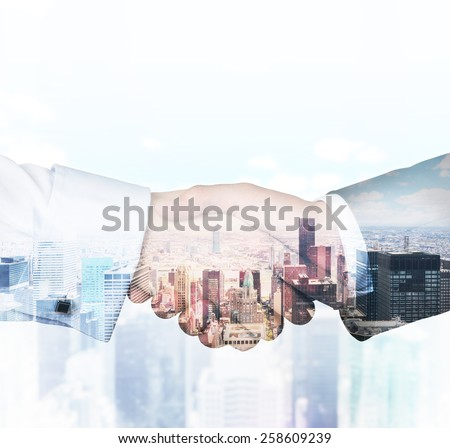 handshake on a building background, double exposure - stock photo