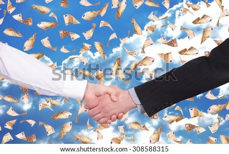 handshake on a flying many 50 euro banknotes background - stock photo