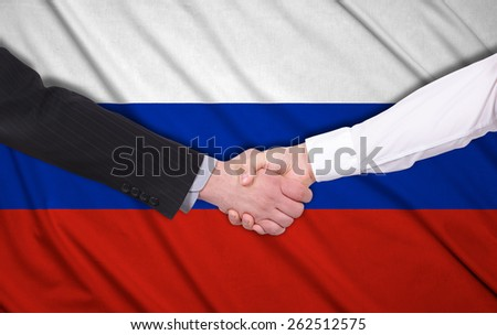 handshake on a Russia flag background - stock photo