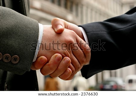 handshake on a street, blurry buildings in the background - stock photo