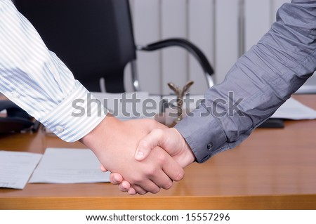 Handshake on background of a table