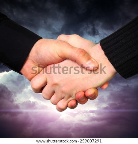 Handshake on Dramatic Cloudscape Area with Ray of Light - stock photo