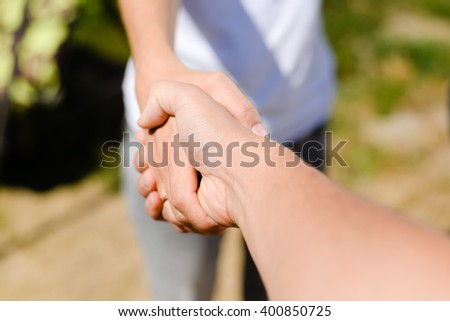 Handshake on outdoors blurred abstract nature background, closeup image - stock photo