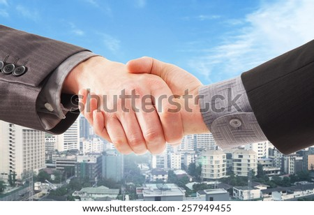 Handshake over a city background - stock photo