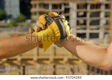 Handshake over building site - stock photo