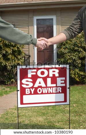 Handshake over home for sale sign - stock photo