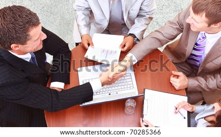 handshake over paper and pen,blurry computer in the background - stock photo