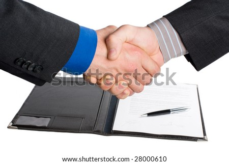 handshake over paper and pen,blurry in the background