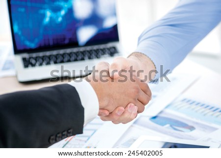 Handshake partners. Two Confident businessman sitting at the negotiating table in the office and shaking hands close-up view of hands. Business people dressed in formal wear - stock photo