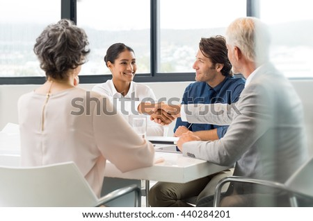 Handshake to seal a deal after a job recruitment meeting. Two business people shaking hands in front of their colleagues. Senior businessman shaking hands to young businesswoman in a modern office.  - stock photo
