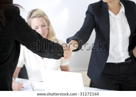Handshake to seal a deal  - with bright office and woman in the background