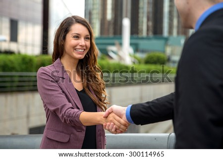 Handshake two business executives downtown buildings man and woman perfect smile teeth hair skin - stock photo